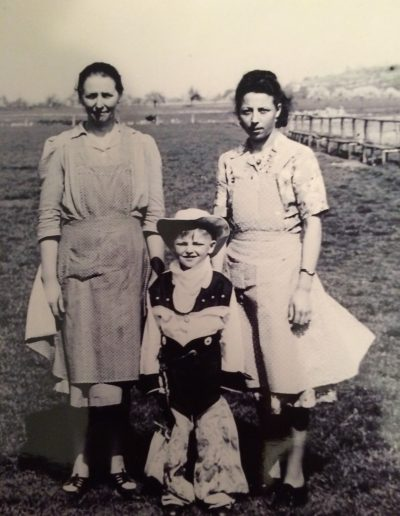 Adam's mom, sister Theresa, and brother Frank wearing the cowboy suit that Adam sent to him for a Christmas gift. Laudenbach, Germany, circa 1954